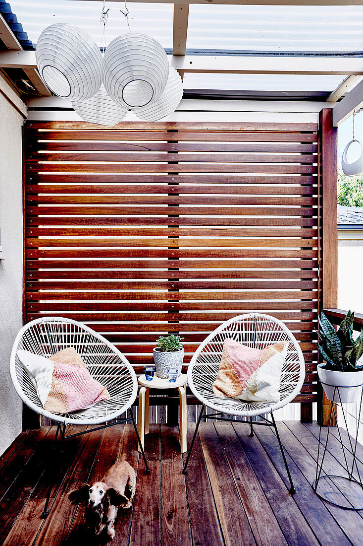 Zwei Designerstühle auf der Terrasse mit Wand aus Latten als Sichtschutz