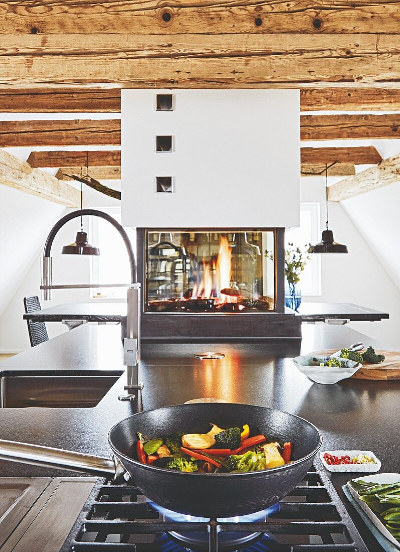 A kitchen island with a gas oven and granite worktop with a gas fire in the background