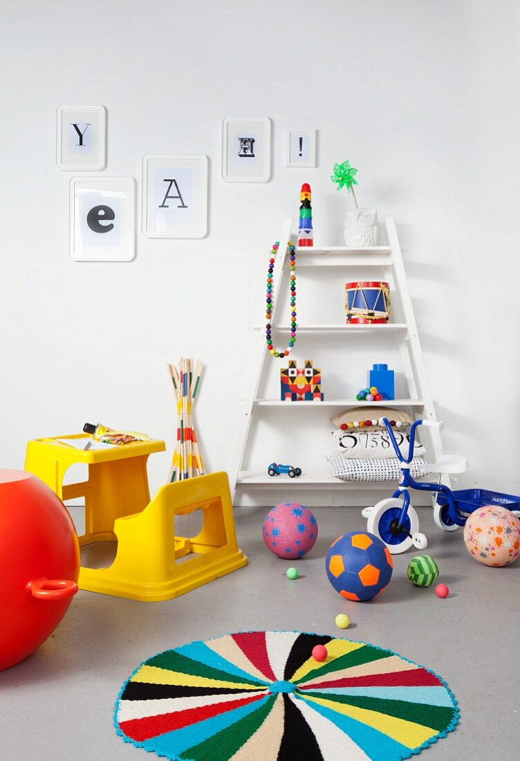 Yellow plastic desk and bench, colourful toys, blue tricycle and white shelves in child's bedroom