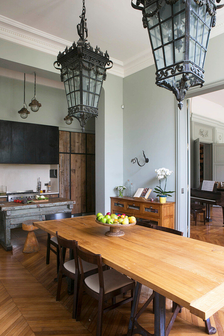 Antique lamps above dining table in front of open-plan kitchen