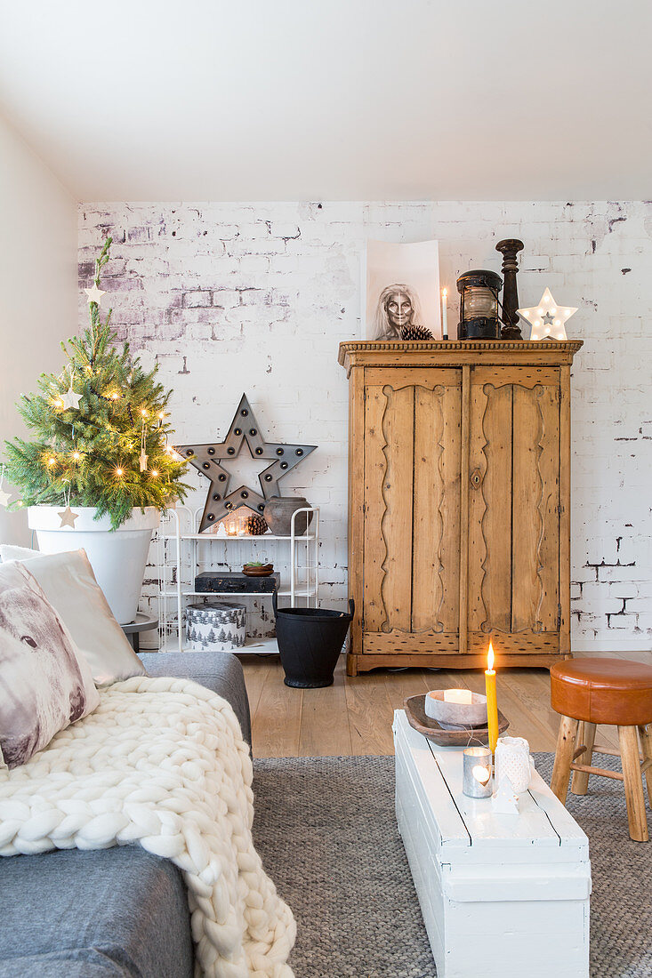 Wooden cupboard against brick wall and Christmas decorations in living room