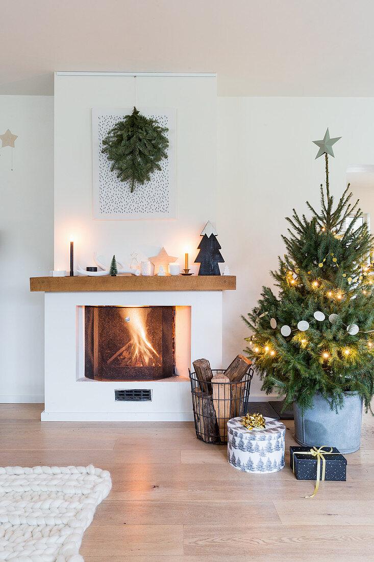 Geschenke unterm Weihnachtsbaum neben dem Kamin mit Feuer