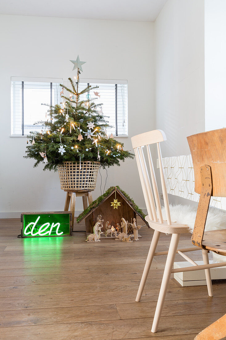Christmas tree, nativity scene and green neon lettering