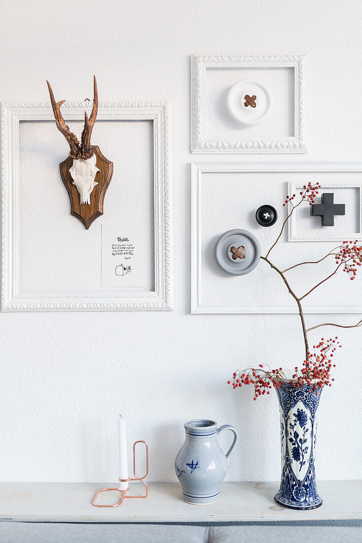 Arrangement of white picture frames and hunting trophies above two vases