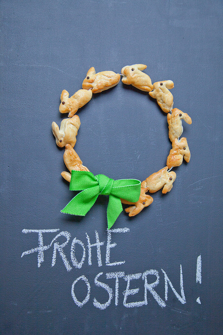 Wreath of pastry bunnies and Easter greeting on chalkboard