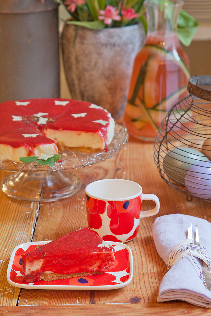 Slice of cake with red glaze on floral plate