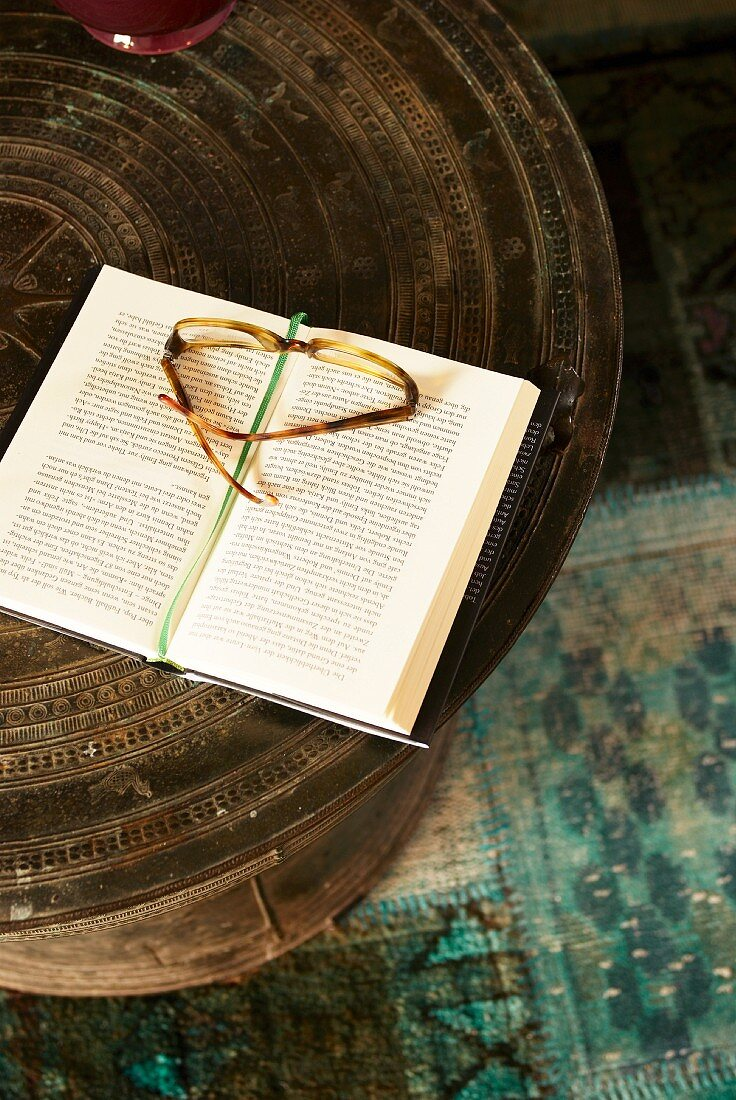 Reading glasses on book on ethnic table