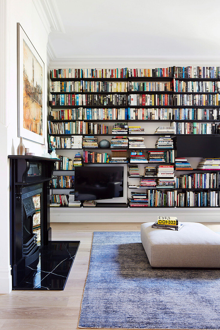 Large bookcase in the living room with an open fireplace