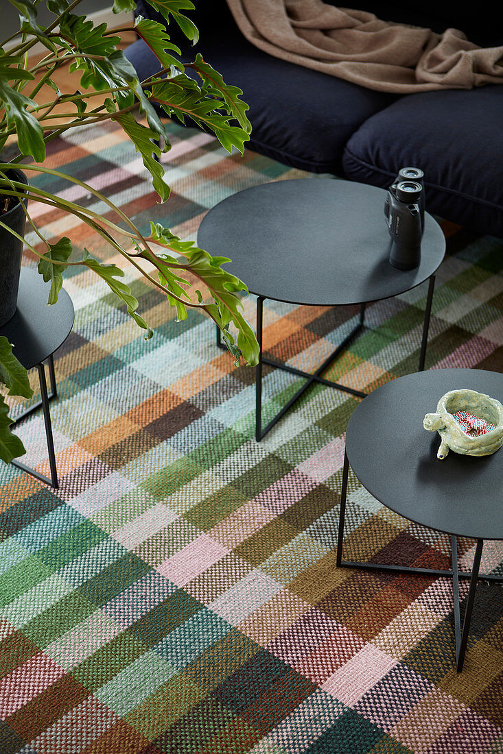 Two black coffee tables on tartan rug in living room
