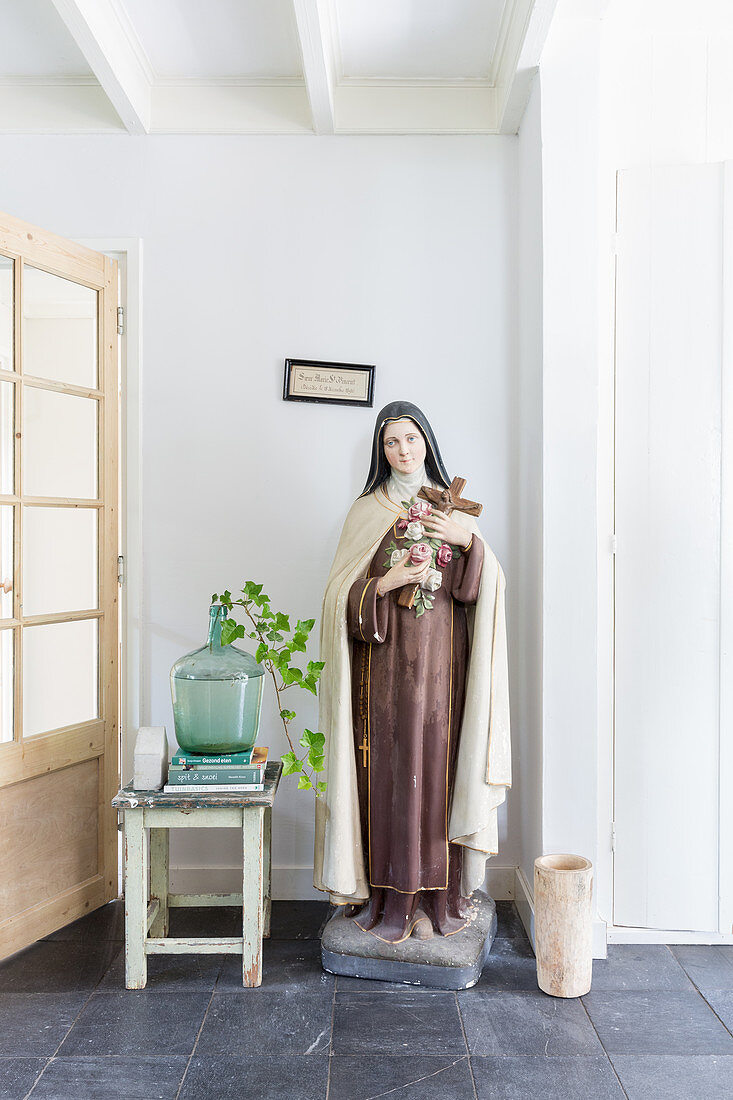 Large statue of the Madonna next to demijohn used as vase on stool