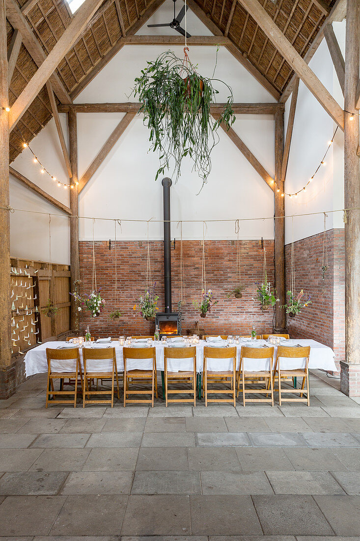 Flower arrangements suspended over set table in converted barn