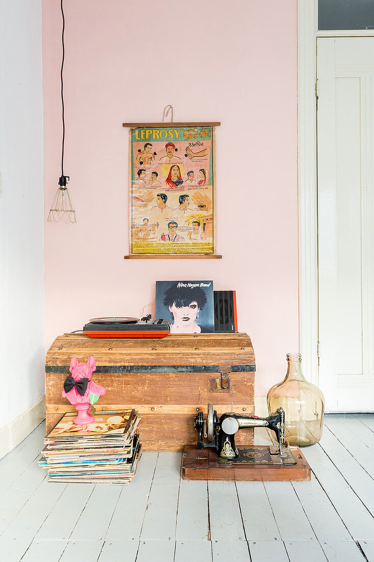 Old trunk and flea-market finds on floor in front of pink wall