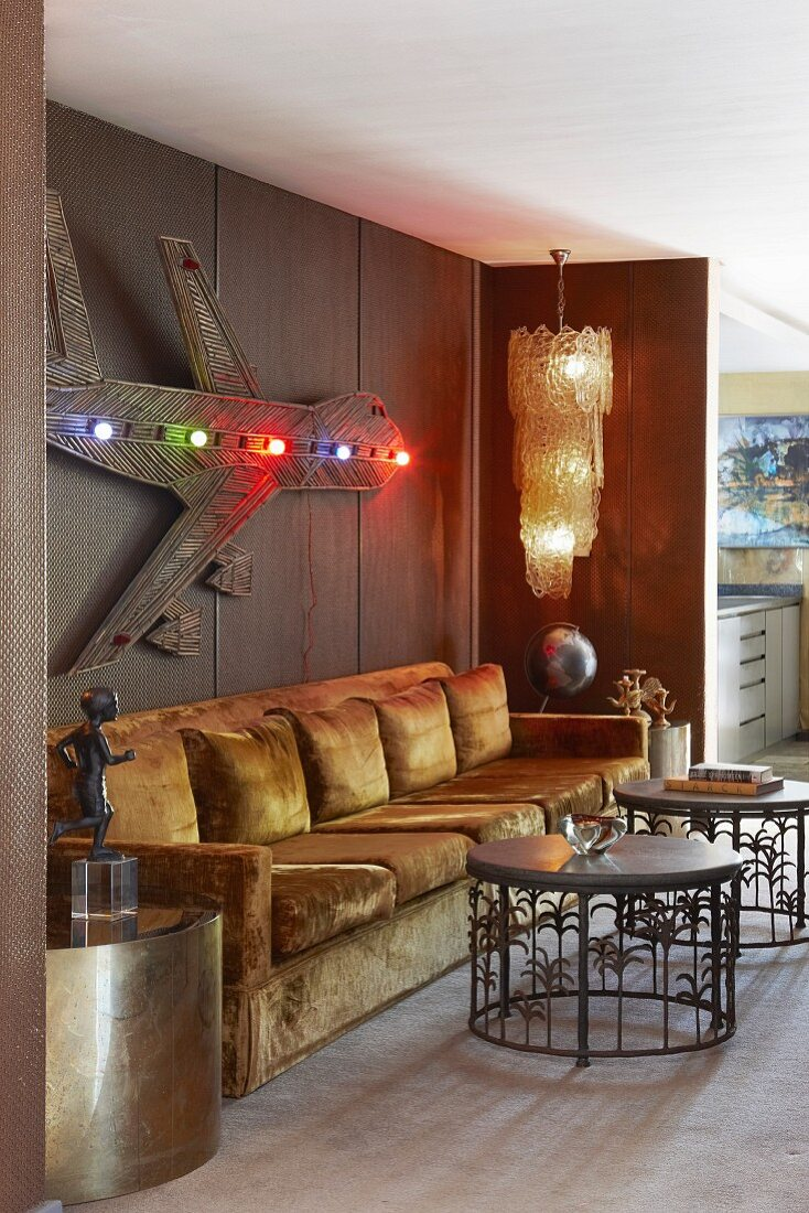 Long gold sofa in niche with metal tables and artwork on wall
