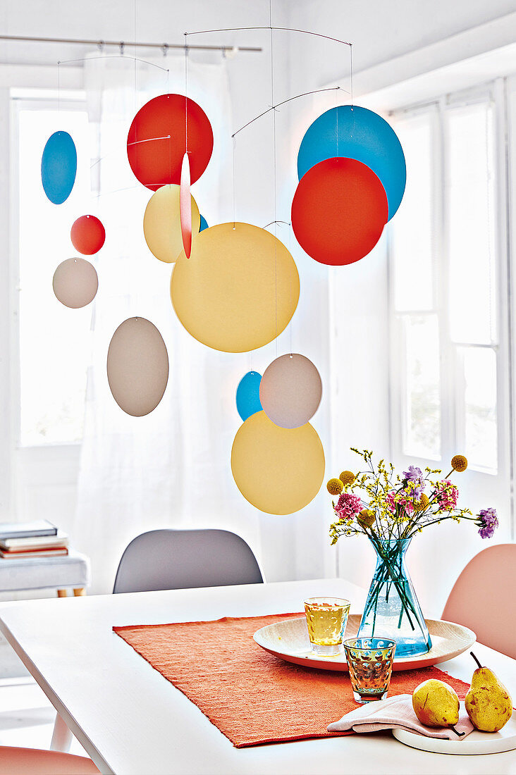 A homemade mobile made from coloured cardboard circles