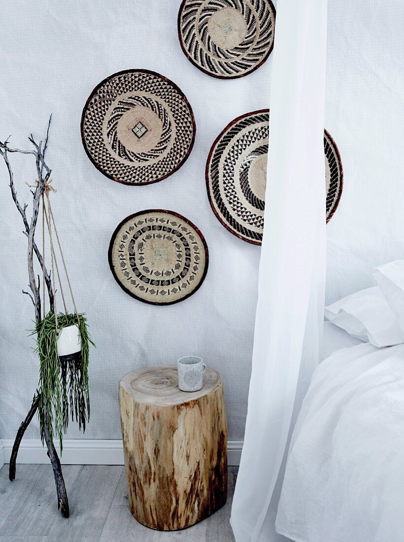 Wall decoration made of baskets over a tree trunk as a bedside table