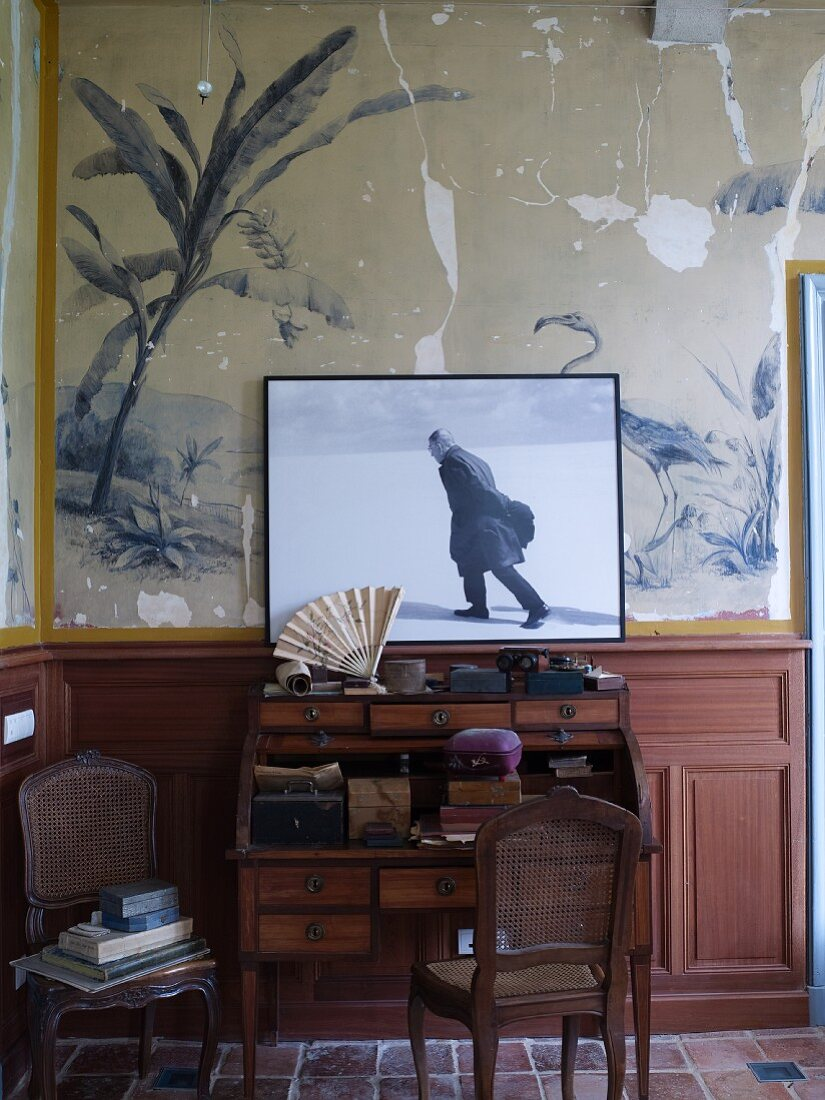 Photo of Satre on top of old writing desk leaning against old mural