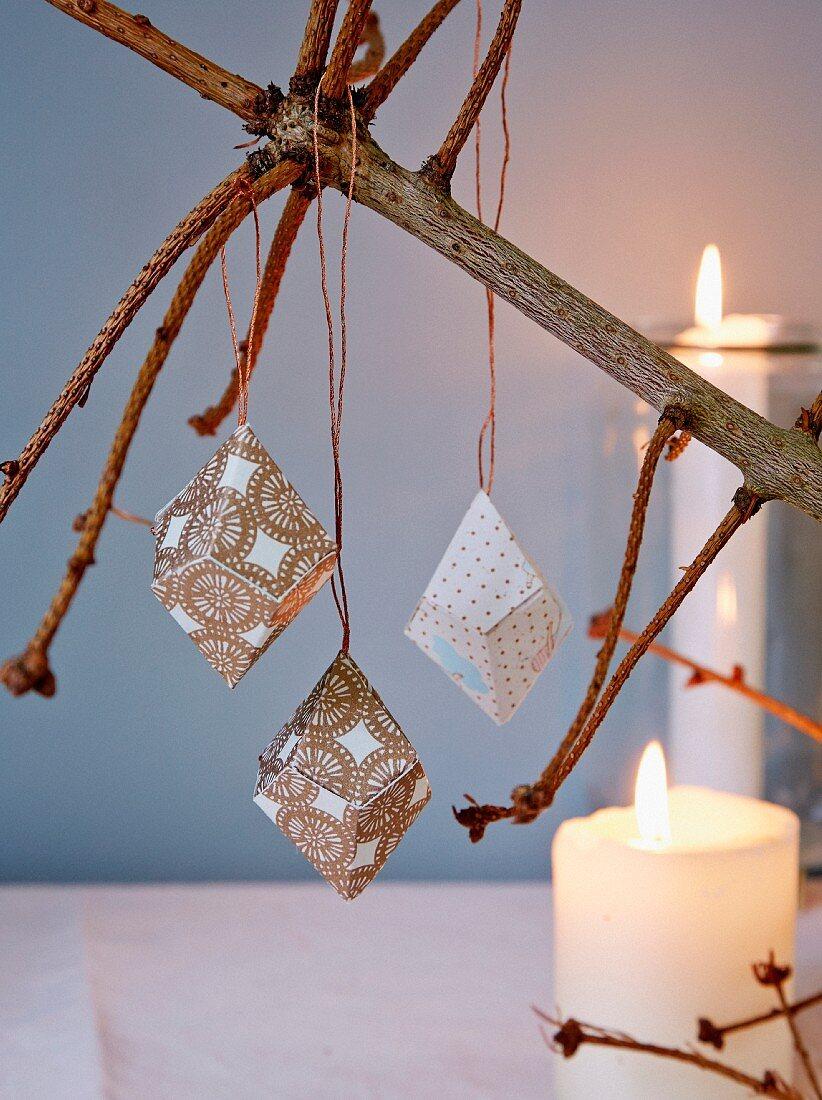 Prismen aus Papier an kahlem Weihnachtsbaum im Kerzenlicht