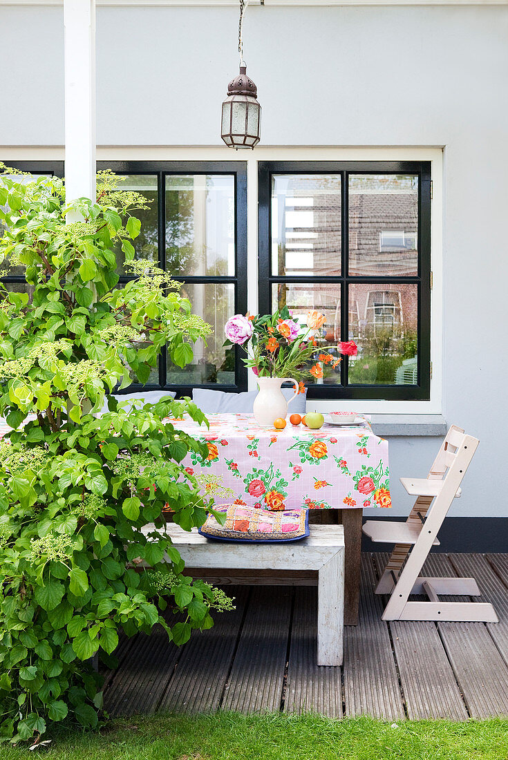 Floral tablecloth and vase of flowers on table on terrace