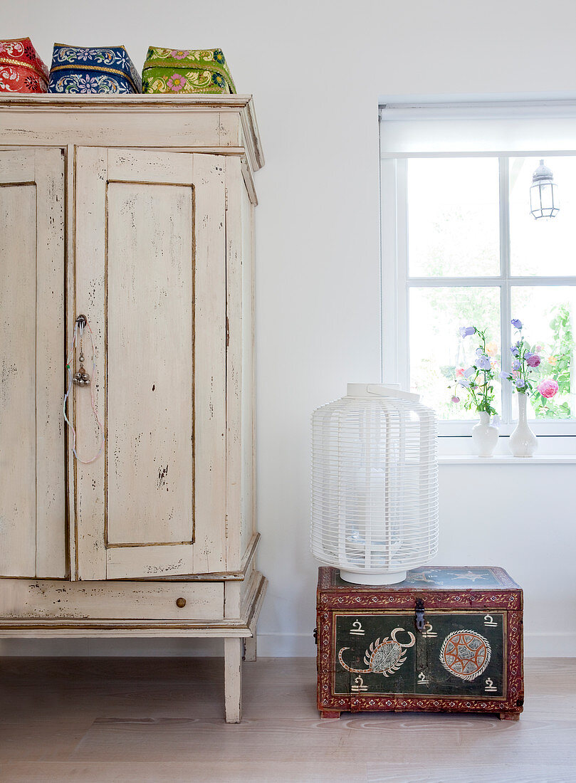 Ethnic trunk and lantern next to white cupboard