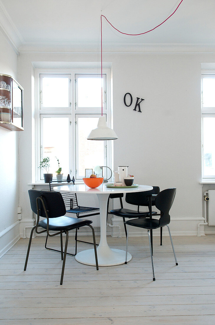 Black chairs around a white designer table in a minimalist dining room