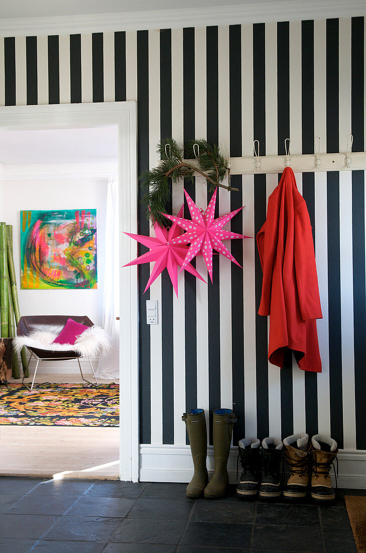 Black and white striped wall in a hallway, pink stars hanging from the hook coat rack