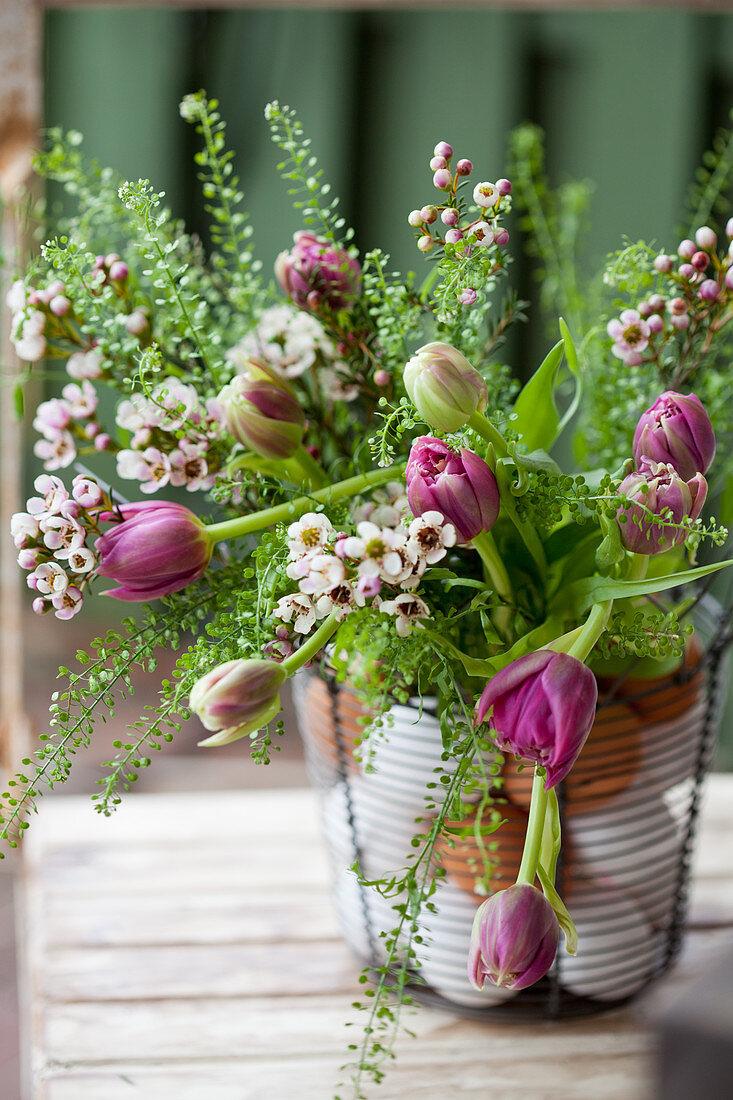 Bouquet of tulips, shepherd's purse and Australian waxflowers in wire basket with eggs