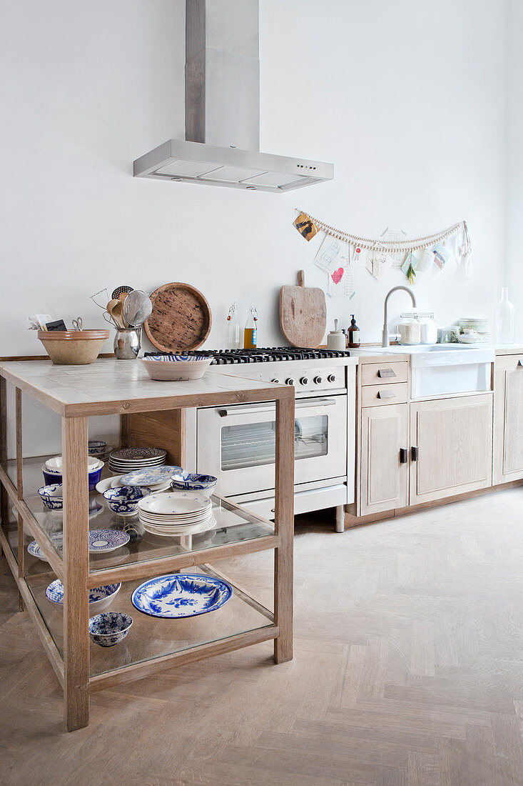 Counter shelf with blue and white dishes in a bright kitchen