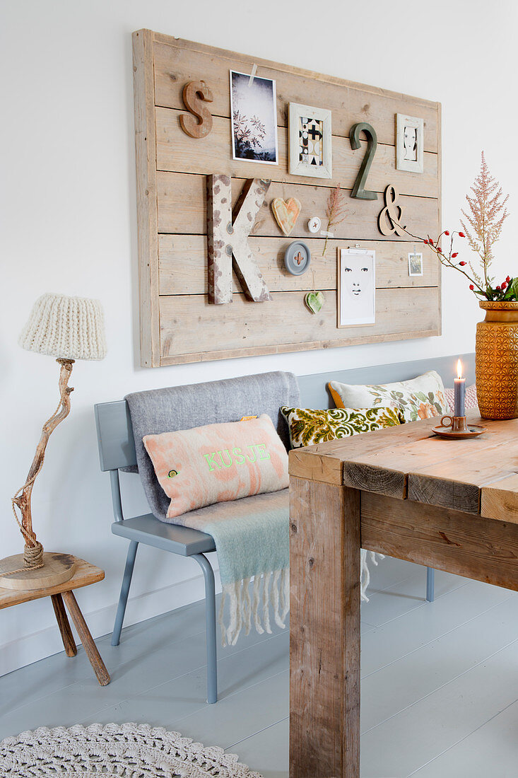 Pinboard made from wooden planks above grey bench and rustic dining table
