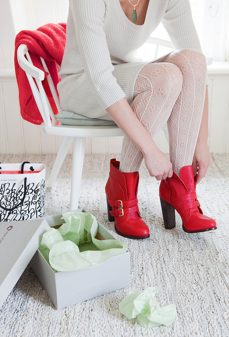 Woman sitting on white chair putting on red boots