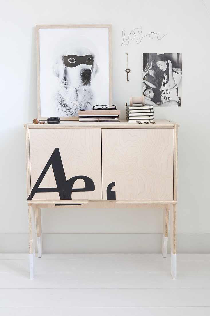 Books on sideboard below black-and-white photos on wall