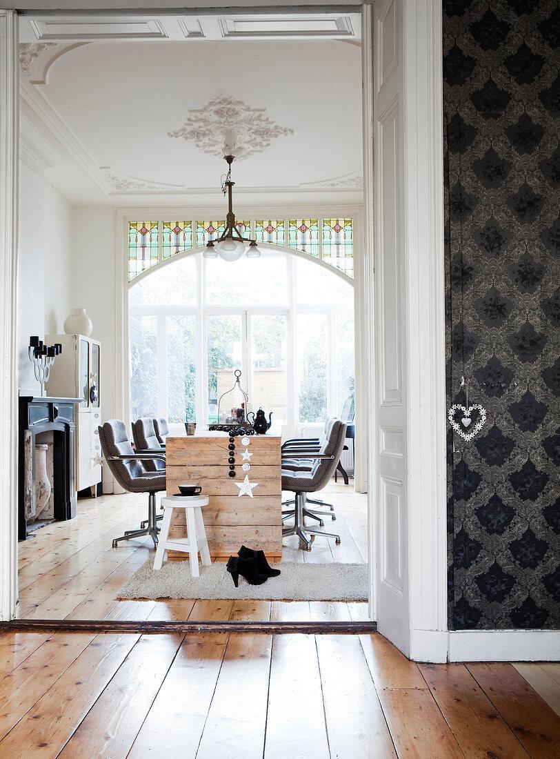 Drehstühle am rustikalen Holztisch in einer Altbauwohnung mit Stuckdecke