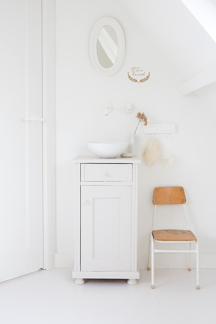 Chair next to sink on white base unit