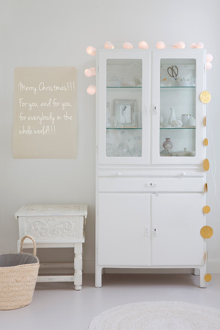 White glass-fronted cabinet decorated with fairy lights and garland next to Christmas greeting on wall