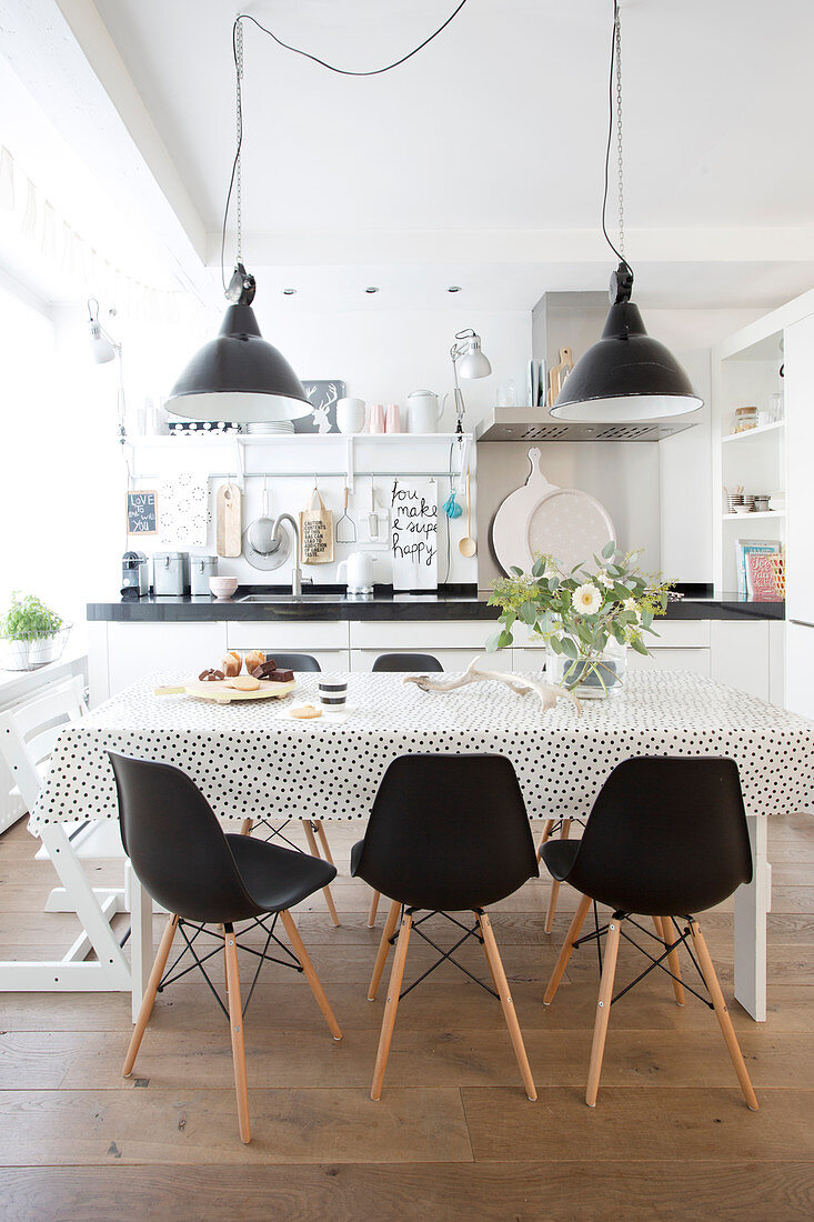 Black-and-white polka-dot tablecloth on dining table and black classic chairs in open-plan kitchen