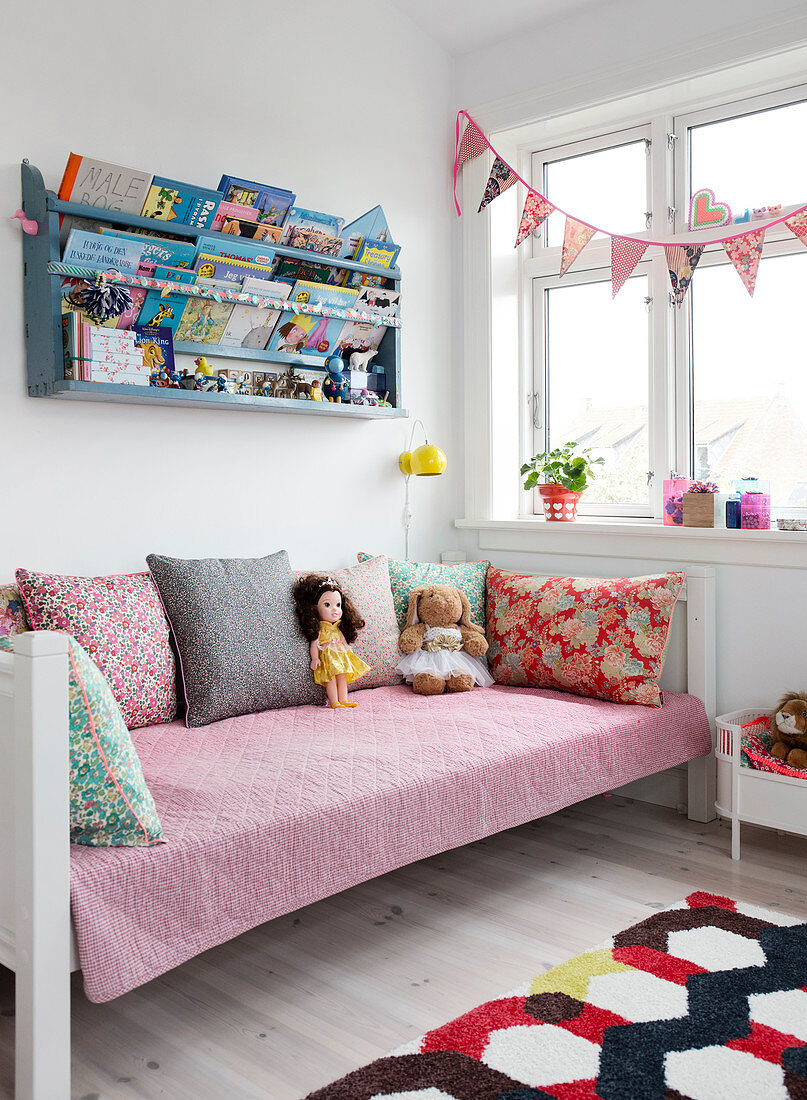 Plate shelf with books above a day bed in a children's room