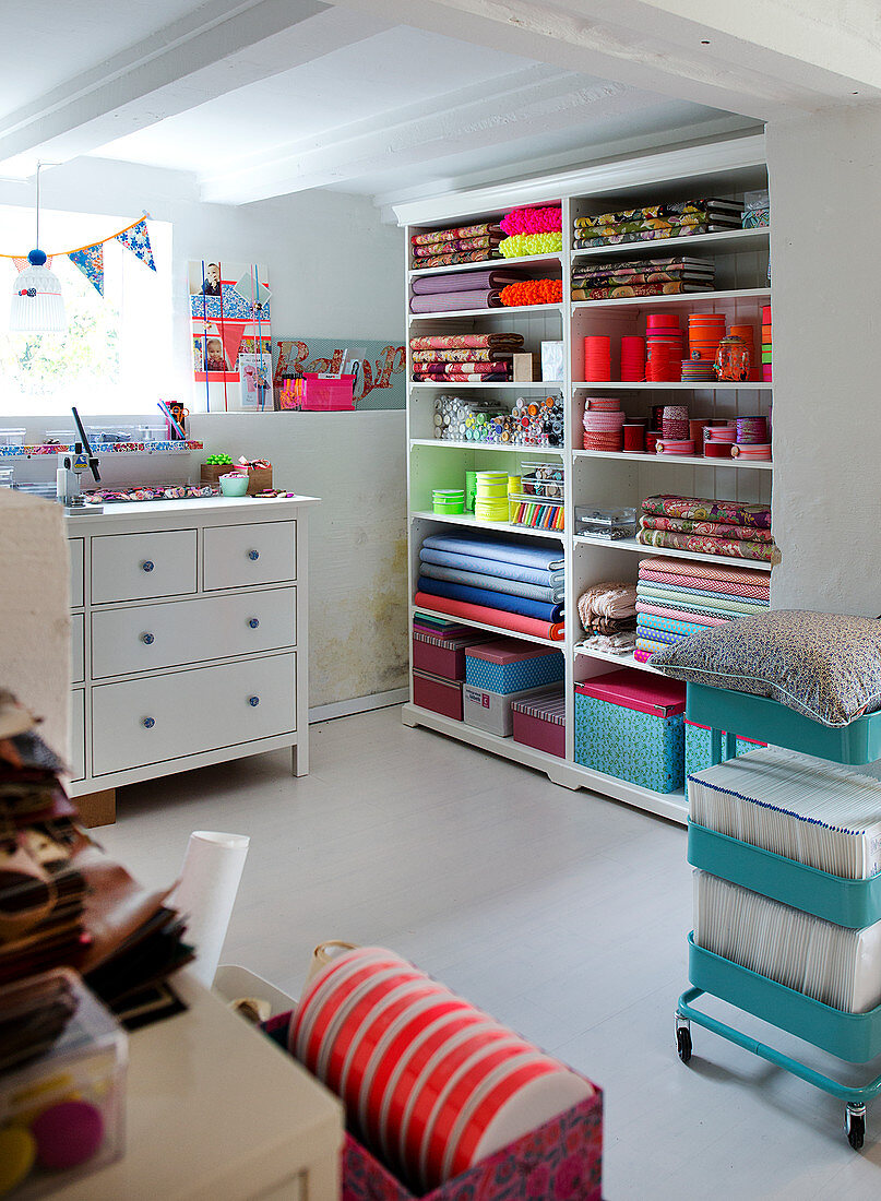 Shelf with colorful fabrics and sewing accessories in the craft room