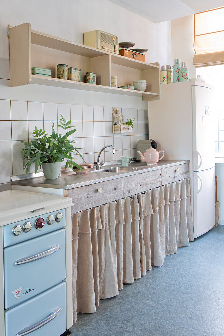 Vintage-style kitchen with curtains on base units