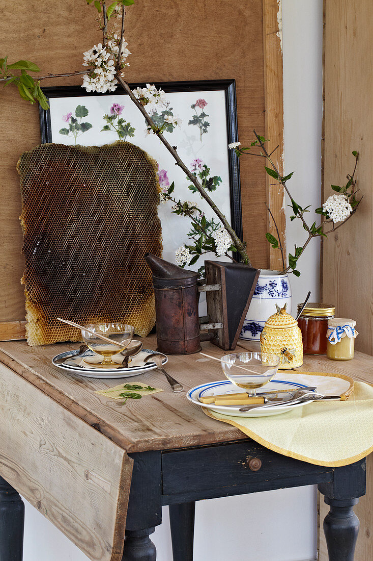 Nostalgically laid table with honey, honeycombs, and branches