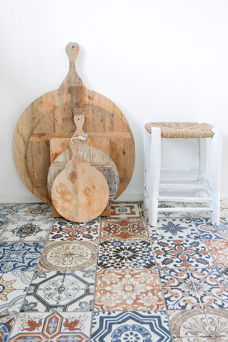 Wooden cutting boards and stools on a Moroccan tiled floor