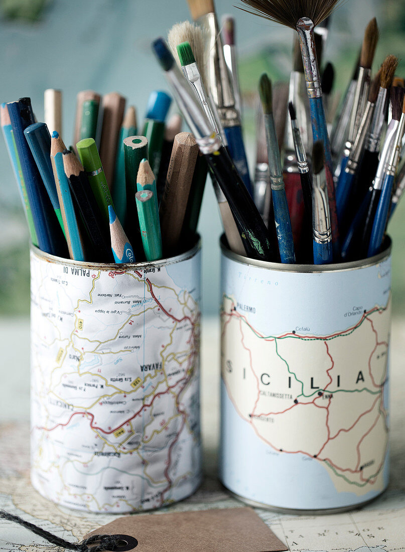 Food cans with maps stuck to them as holders for pens and brushes