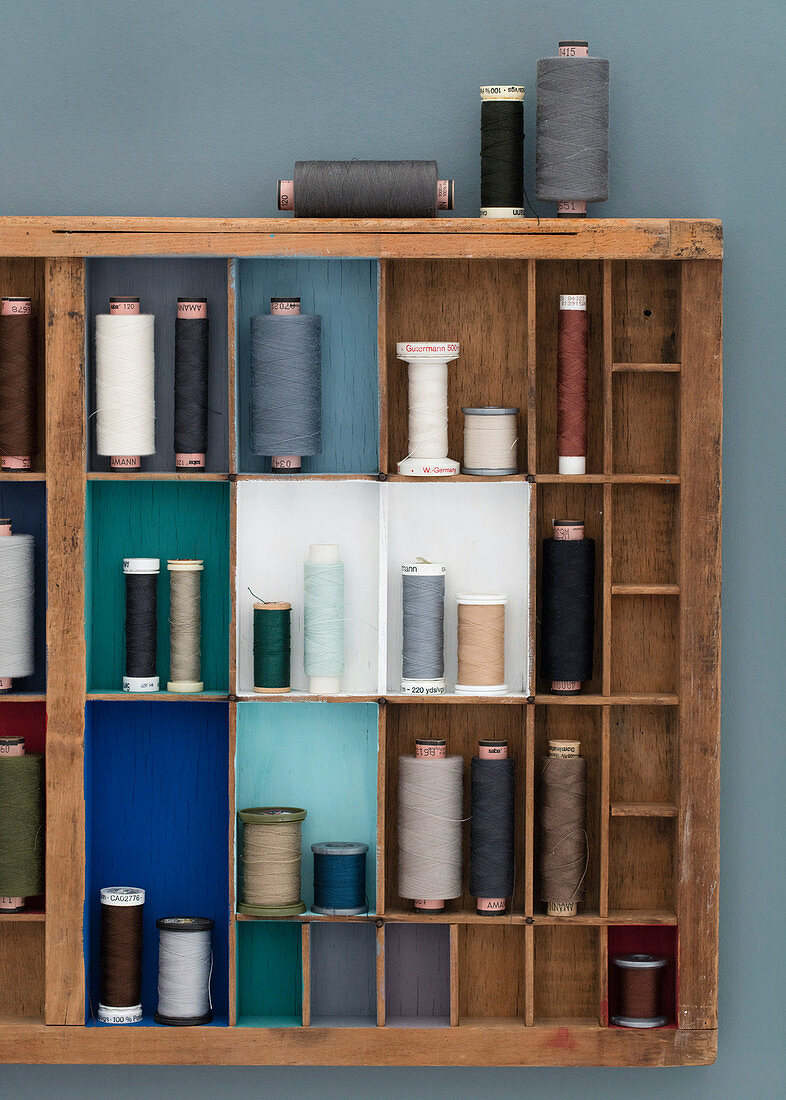 Typecase with painted compartments and spools of thread