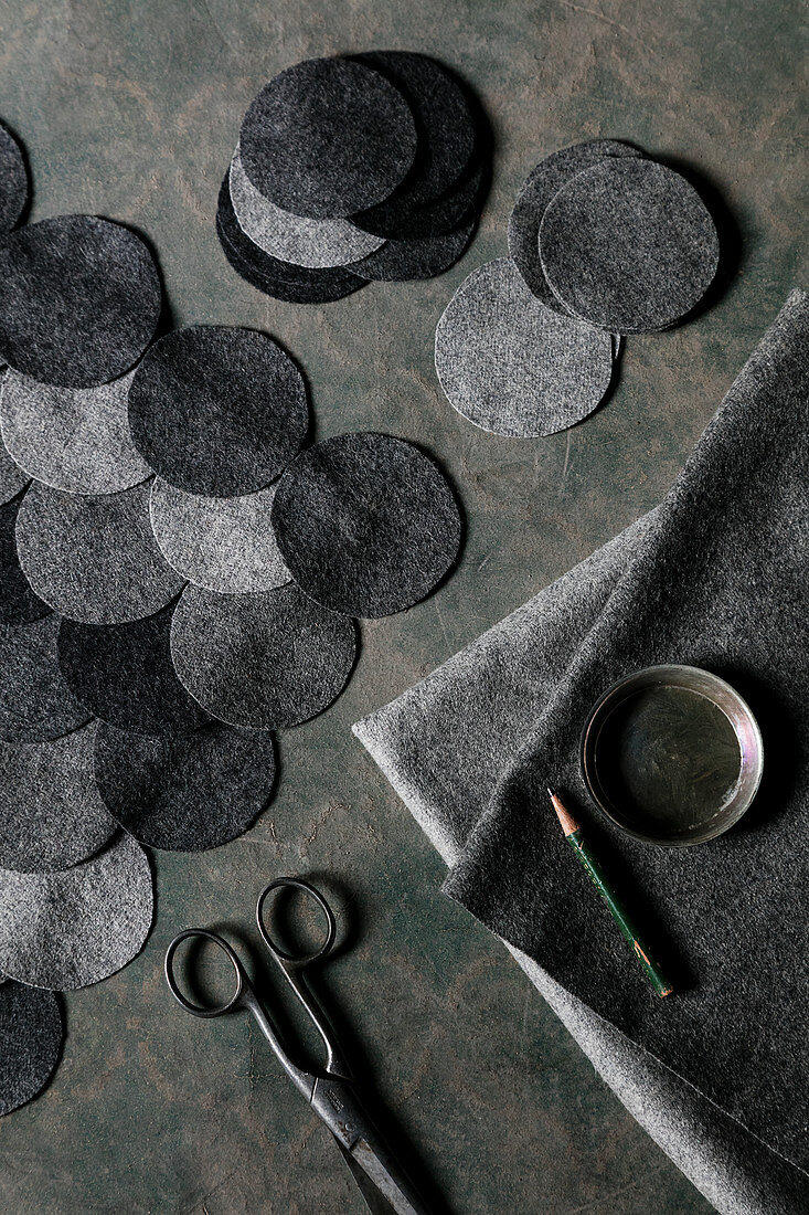 A DIY cushion cover made from grey felt circles