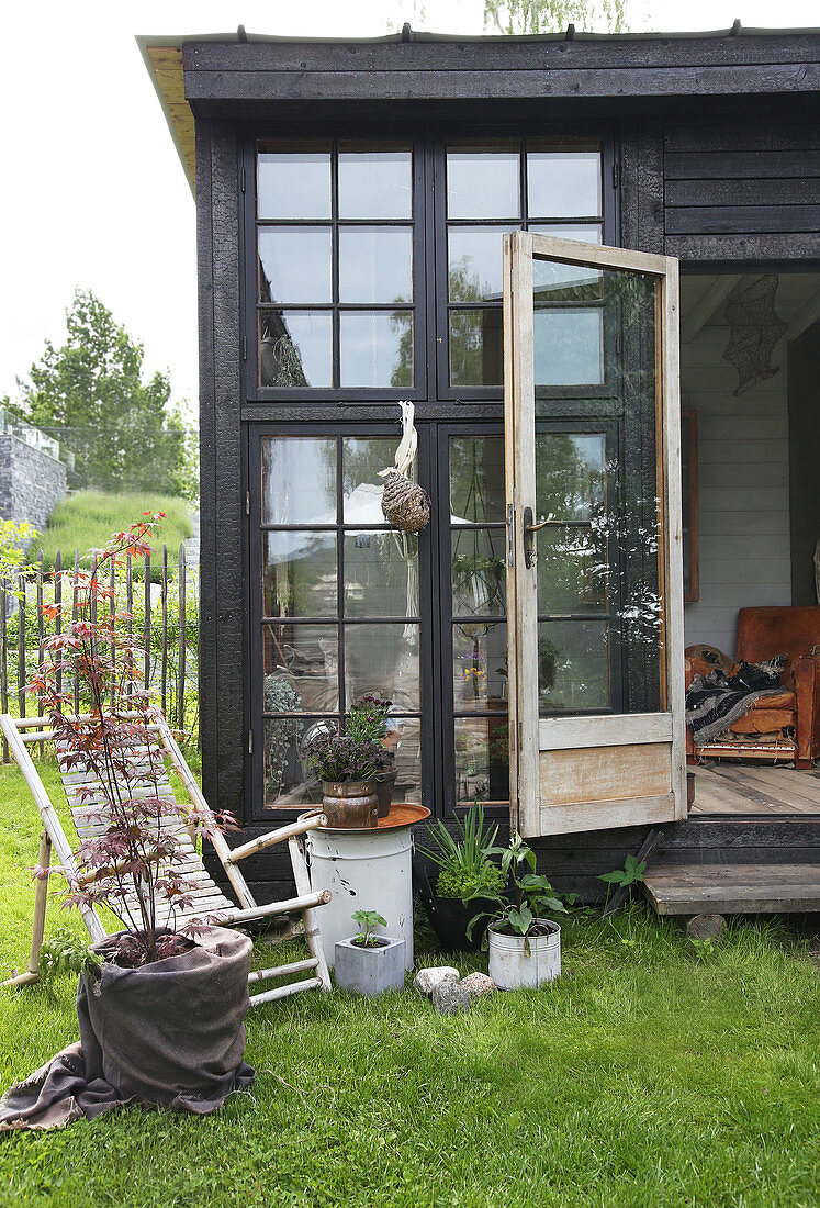 A bamboo chair in front of a glass house made from recycled materials