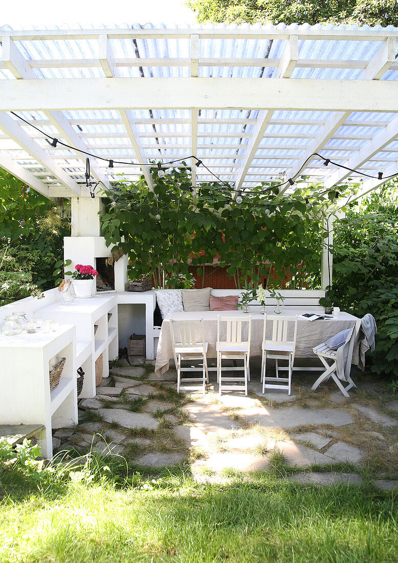 A dining table with chairs and a bench with green plants on a covered terrace