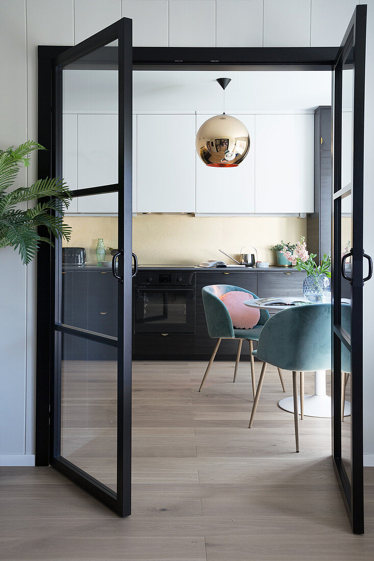A view through an open glass door into a kitchen with a round table and shell chairs