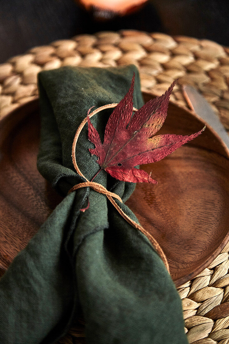 A place setting decorated with an autumn leaf