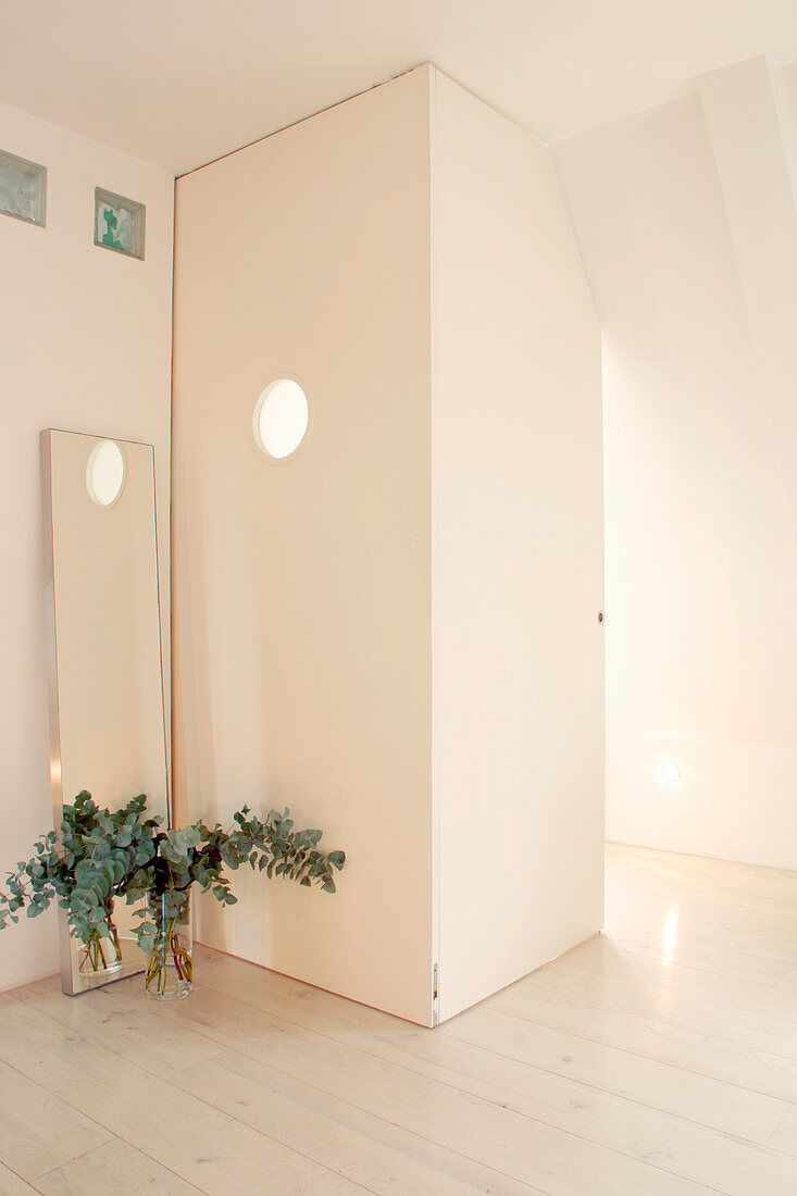 Room within a room with a porthole under the sloping ceiling