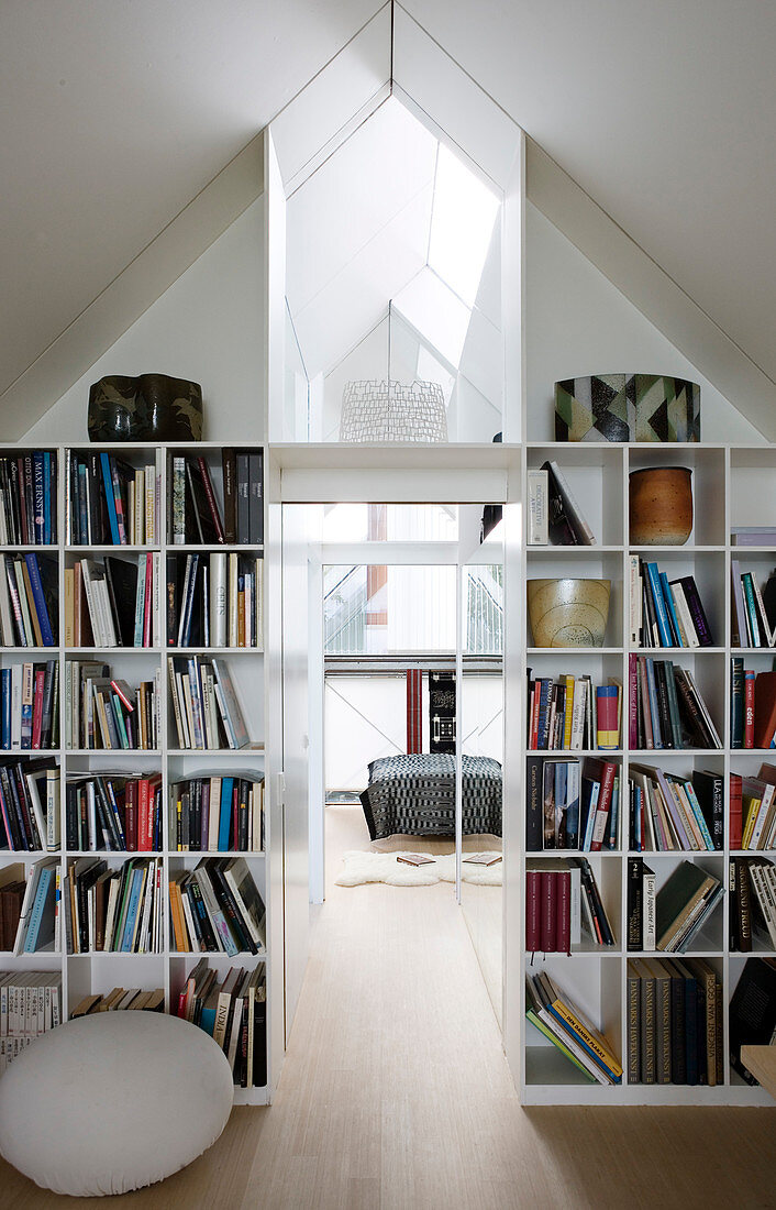 Bookshelves in a partition wall under the sloping roof with a view of a bedroom