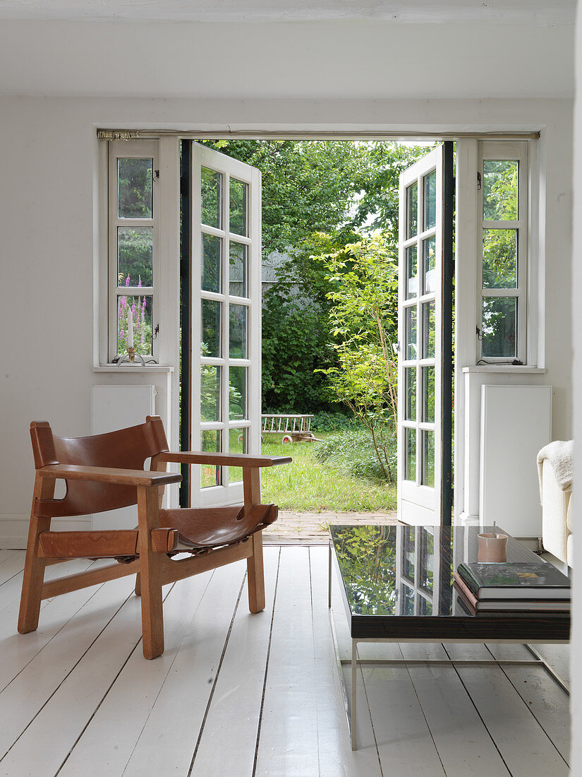 Wooden and leather side Armchair in a living room with access to the garden