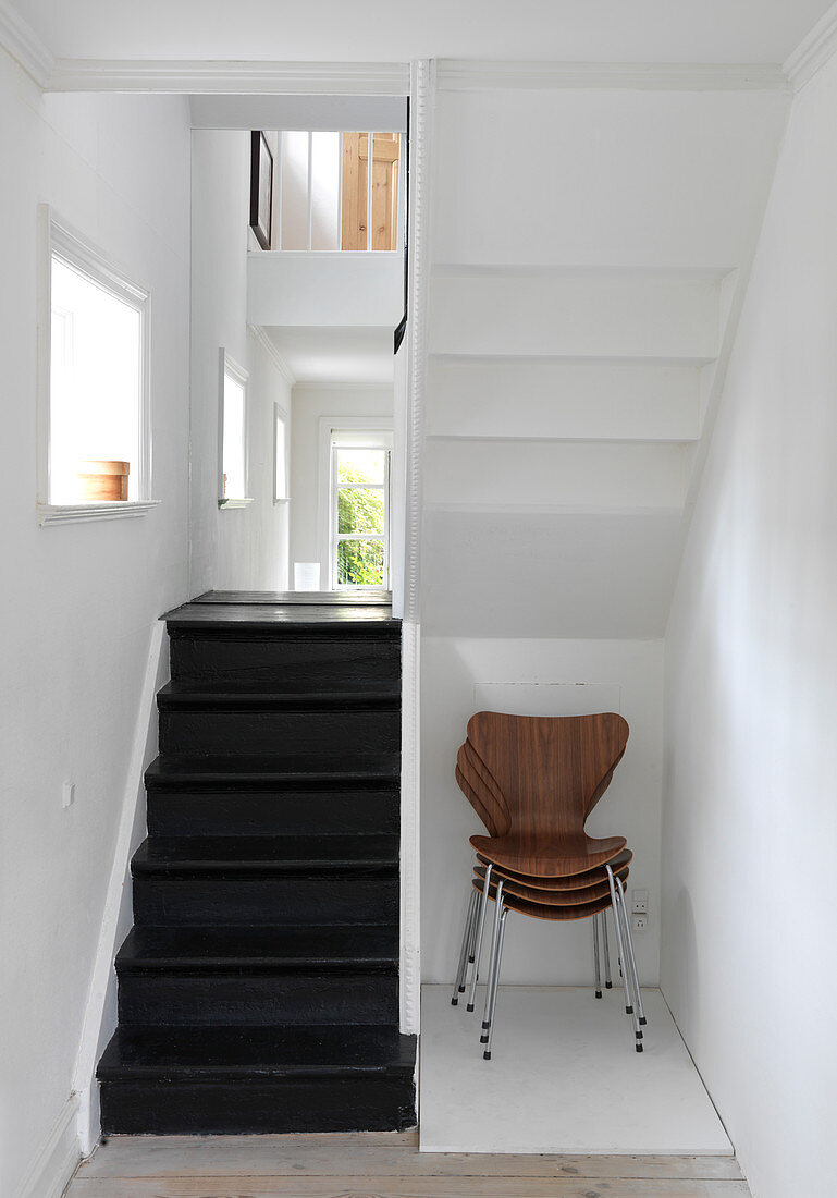 Stack of designer chairs under the stairs with black steps
